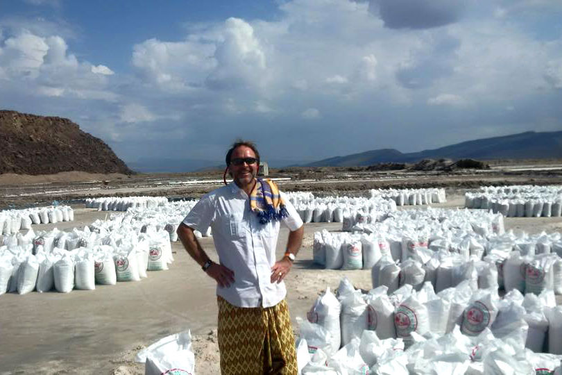 CGA's Warren Creates standing in front of bags of salt gathered by the Afar at the Lake Dobi Salt Pans in Ethiopia, near the border with Djibouti.